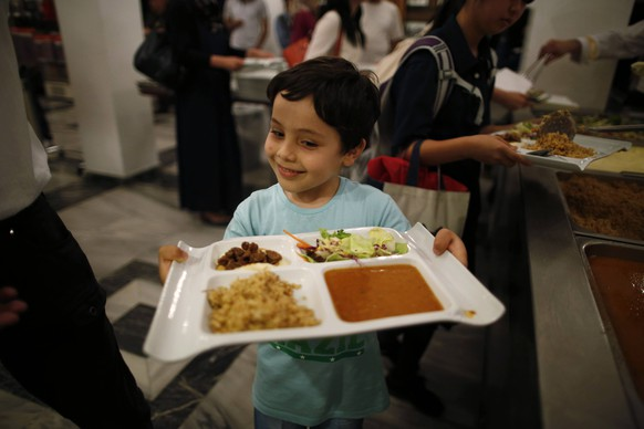 A Muslim boy residing in Japan have his iftar, breaking of fast meal, during the holy month of Ramadan at Tokyo Camii mosque in Tokyo June 29, 2014. REUTERS/Issei Kato (JAPAN - Tags: RELIGION FOOD)