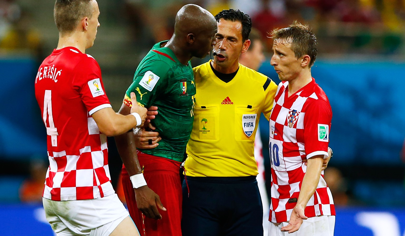 MANAUS, BRAZIL - JUNE 18: Referee Pedro Proenca separates Stephane Mbia of Cameroon and Luka Modric of Croatia during the 2014 FIFA World Cup Brazil Group A match between Cameroon and Croatia at Arena Amazonia on June 18, 2014 in Manaus, Brazil.  (Photo by Matthew Lewis/Getty Images)