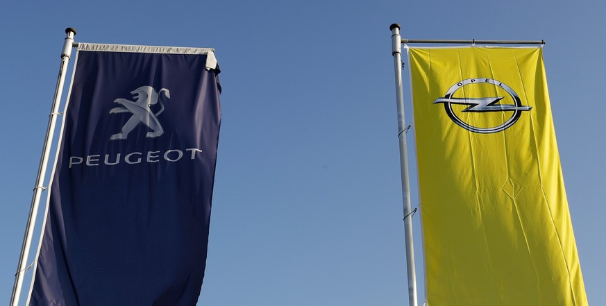 epa05792930 Flags with a logo of Opel and Peugeot fly at a car dealer in Darmstadt, Germany, 14 February 2017. According to media reports on 14 February 2017, French carmaker PSA Group is exploring the acquisition of General Motor's European Opel brand.  EPA/RONALD WITTEK