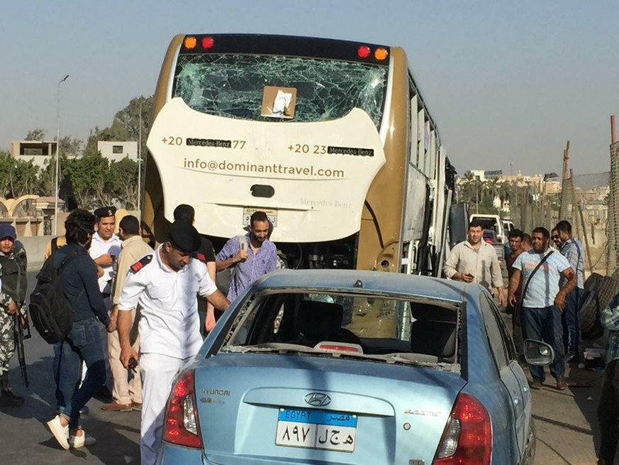 CORRECTS DATE PHOTO TAKEN - Police inspect a car and a bus that were damaged by a bomb, in Cairo, Egypt, Sunday, May 19, 2019. Egyptian officials say a roadside bomb has hit a tourist bus near the Giza Pyramids. They said Sunday's blast wounded at least 17 people including tourists. (AP Photo/Mohammed Salah)