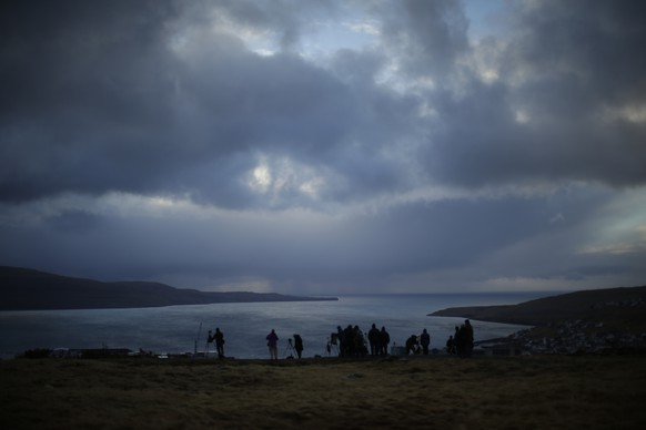 People wait for the start of a total solar eclipse from a hill beside a hotel overlooking the sea and Torshavn, the capital city of the Faeroe Islands, Friday, March 20, 2015. For months, even years, accommodation on the remote Faeroe Islands has been booked out by fans who don't want to miss an almost three-minute-long astronomical sensation. Now they just have to hope the clouds will blow away so they can fully experience Friday's brief total solar eclipse.  (AP Photo/Matt Dunham)