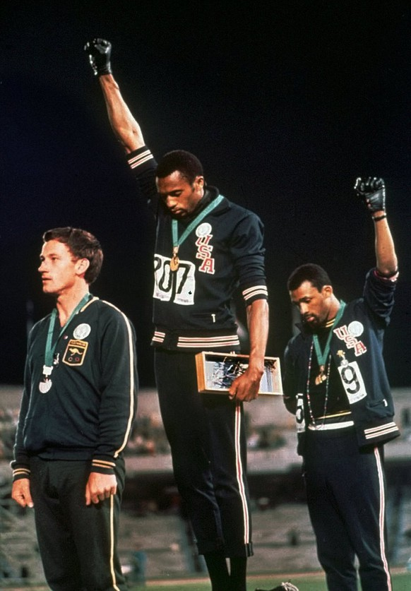 Extending gloved hands skyward in racial protest, U.S. athletes Tommie Smith, center, and John Carlos, stare downward during the playing of the Star Spangled Banner after Smith received the gold and Carlos the bronze for the 200 meter run at the Olympics in Mexico City on October 16, 1968. Australian silver medalist Peter Norman is at left. (KEYSTONE/AP/Str)  [SIEHE IMAGE ID 1871420]