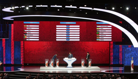 epa04860222 FIFA Secretary General Jerome Valcke (C) and draw assistants Samuel Eto'o (L) and Rinat Dassayev (R) conduct the Preliminary Draw of the FIFA World Cup 2018 at Konstantinovsky palace outside St.Petersburg, Russia, 25 July 2015. St.Petersburg is one of the host cities of the FIFA World Cup 2018 in Russia which will take place from 14 June until 15 July 2018.  EPA/MAXIM SHIPENKOV