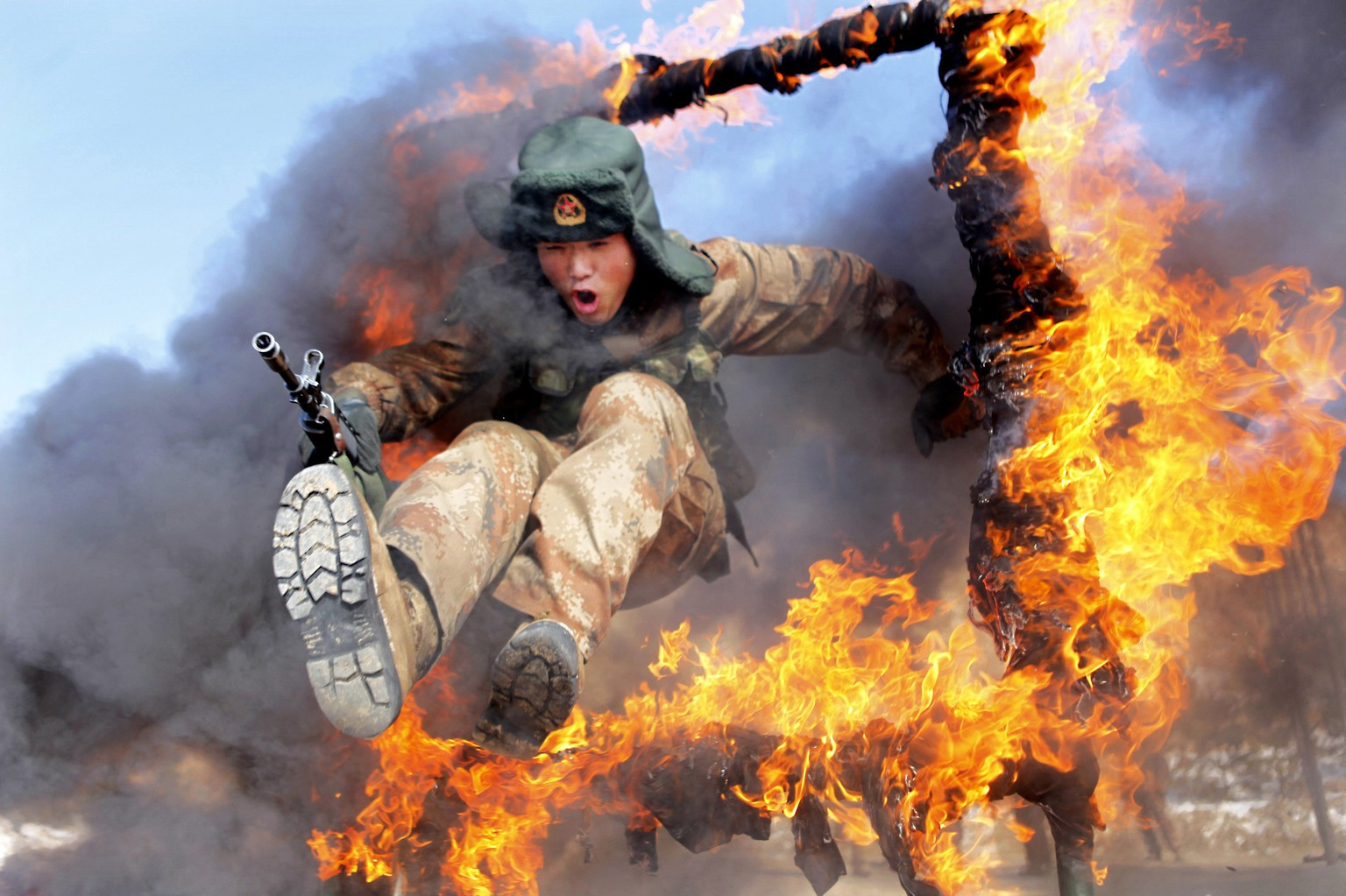 A frontier soldier from the People's Liberation Army jumps through a ring of fire as part of training in Heihe, Heilongjiang province, March 5, 2014. REUTERS/China Daily (CHINA - Tags: MILITARY TPX IMAGES OF THE DAY) CHINA OUT. NO COMMERCIAL OR EDITORIAL SALES IN CHINA