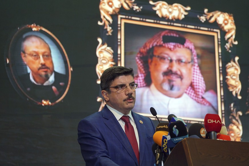 FILE - In this Sunday, Nov. 11, 2018 file photo, Yasin Aktay, an advisor to Turkey's President Recep Tayyip Erdogan, speaks during an event organized to mark the 40th day of the death of Saudi writer Jamal Khashoggi, background, in Istanbul, Turkey. Saud Al-Mojeb, Saudi Arabia's top prosecutor, is recommending the death penalty for five suspects charged with ordering and carrying out the killing of Saudi writer Jamal Khashoggi. Al-Mojeb told a press conference in Riyadh Thursday, Nov. 15, 2018,  that Khashoggi's killers had been planning the operation since September 29, three days before he was killed inside the kingdom's consulate in Istanbul. (AP Photo/Neyran Elden, File)