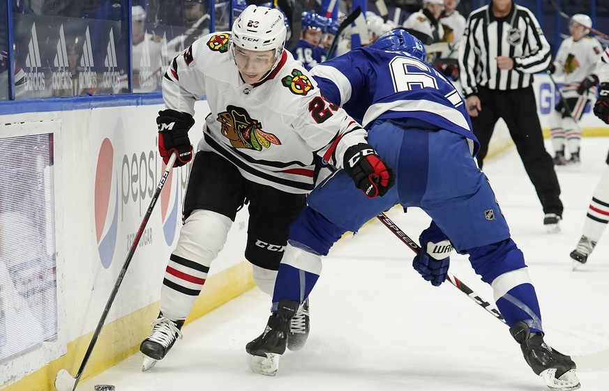 Chicago Blackhawks center Philipp Kurashev (23) slips between Tampa Bay Lightning center Mitchell Stephens (67) and the dasher during the first period of an NHL hockey game Friday, Jan. 15, 2021, in Tampa, Fla. (AP Photo/Chris O'Meara)