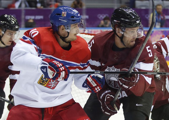 Czech Republic forward Roman Cervenka scrambles after a rebound against Latvia forward Janis Sprukts in the first period of a men's ice hockey game at the 2014 Winter Olympics, Friday, Feb. 14, 2014, in Sochi, Russia. (AP Photo/Mark Humphrey)