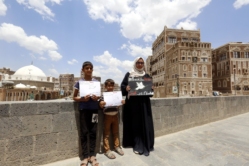 epa06999446 Yemeni female activist Haifa Subay (R) and children hold pro-peace placards during a campaign calling for peace in the war-torn country, in the old quarter of Sana'a, Yemen, 05 September 2018. Yemeni activist and artist Haifa Subay, 27, has launched a 'Dove Campaign' to highlight the victims of over three years of the war in Yemen and encourage people to get more involved in promoting peace and raising awareness of the ongoing war between the internationally recognized Yemeni government and the Houthi rebels, which led to the deaths of over 6,600 civilians and left 22 million people in urgent need of aid since 2015.  EPA/YAHYA ARHAB