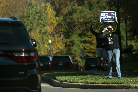 In this image made through the window of the press vehicle accompanying the motorcade carrying President Donald Trump, people hold signs at the entrance of Trump National Golf Club, Sunday, Nov. 8, 2020, in Sterling, Va. (AP Photo/Evan Vucci) Donald Trump