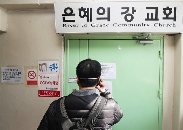 epa08296731 A man takes a photograph at the gate to the temporarily closed River of Grace Community Church in Seongnam, South Korea, 16 March 2020. The church will be closed until March 22 after 46 people, including its pastor and his wife, were confirmed to have been infected with the new coronavirus.  EPA/YONHAP SOUTH KOREA OUT