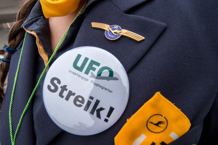 epa05014224 A members of the German cabin crew and flight attendants union 'UFO' wears a huge button as a group gathers for a rally at Frankfurt International Airport in Frankfurt/Main, Germany, 06 November 2015. Lufthansa cancelled 290 flights after its flight attendants announced the first stoppages in a rolling eight-day strike in defence of their retirement benefits. The union, Ufo, is demanding preservation of retirement benefits that enable many stewards to retire from 55. The strike threatens to pull the airline group back into the red after a quarter where its earnings rose by half and it forecast a strong full year.  EPA/BORIS ROESSLER