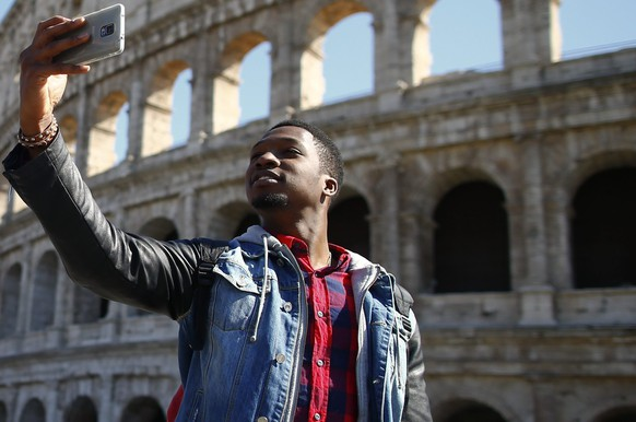 Tourists take a selfie in front of the Colosseum in Rome March 12, 2015. The euro pulled out of its recent dive on Thursday, chalking up its biggest rise against the dollar in a month, after a week of breakneck moves in the world's two biggest currencies. REUTERS/Tony Gentile  (ITALY - Tags: BUSINESS TRAVEL)