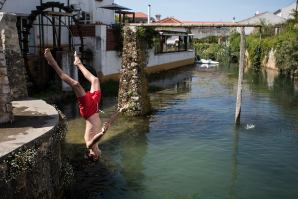 "epa06922153 Locals refreshing themselves on Lis river in Leiria, center of Portugal, 01 August 2018. The Portuguese Institute of the Sea and Atmosphere (IPMA), warns that the maximum temperatures will be ""well above the normal values for the time"", close to 40ºC.  EPA/PAULO CUNHA"