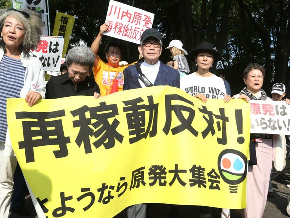 Anti-nuclear demonstrations, including Nobel literature laureate Kenzaburo Oe (C), march in Tokyo on September 23, 2014. Some 16,000 people rallied in the Japanese capital against the government's plan to restart nuclear reactors, more than three years after the Fukushima disaster, local media reported.   JAPAN OUT       AFP PHOTO / JIJI PRESS
