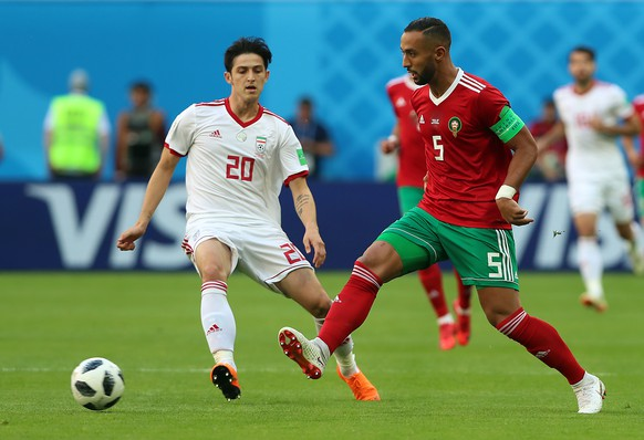 epa06810564 Mehdi Benatia of Morocco (R) and Sardar Azmoun of Iran in action during the FIFA World Cup 2018 group B preliminary round soccer match between Morocco and Iran in St.Petersburg, Russia, 15 June 2018.  (RESTRICTIONS APPLY: Editorial Use Only, not used in association with any commercial entity - Images must not be used in any form of alert service or push service of any kind including via mobile alert services, downloads to mobile devices or MMS messaging - Images must appear as still images and must not emulate match action video footage - No alteration is made to, and no text or image is superimposed over, any published image which: (a) intentionally obscures or removes a sponsor identification image; or (b) adds or overlays the commercial identification of any third party which is not officially associated with the FIFA World Cup)  EPA/TOLGA BOZOGLU   EDITORIAL USE ONLY