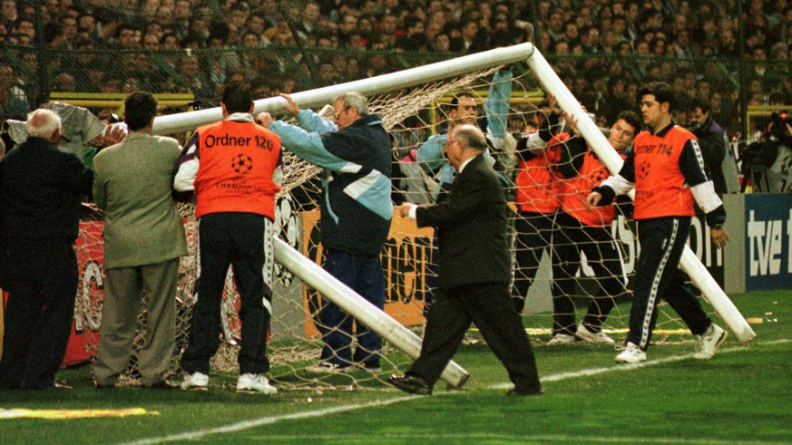 FILE - Real Madrid officials try to raise the goalposts after a fence retaining soccer fans collapsed, knocking down the goalposts prior to the European Champion's League 1st leg semi final match to be played between Real Madrid and Borussia Dortmund in the Santiago Bernabeu stadium April 1, 1998. UEFA anounced Sunday that Real Madrid will be fined 1.3 million Swiss francs ($850,000) for the incidents and banned from playing their next two European  games at home. (AP Photo/Karl-Heinz Kreifelts)