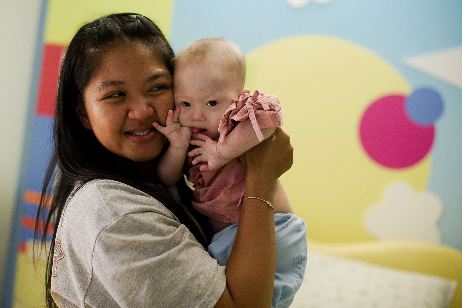 "Thai surrogate mother Pattaramon Chanbua (L) holds her baby Gammy, born with Down Syndrome, at the Samitivej hospital, Sriracha district in Chonburi province on August 4, 2014. The surrogate mother of a baby reportedly abandoned by his Australian parents in Thailand because he has Down Syndrome was a ""saint"" and ""absolute hero"", Australian Immigration Minister Scott Morrison said. AFP PHOTO / Nicolas ASFOURI"