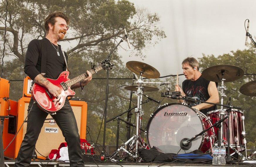 FILE - In this Sept. 11, 2015 file photo, Jesse Hughes, left, and Jeff Friedl with Eagles of Death Metal perform at Riot Fest & Carnival in Douglas Park in Chicago. Hughes, frontman of the U.S. band whose Nov. 13 performance at the Bataclan theater in Paris was stormed by Islamic extremist suicide bombers, says he feels a