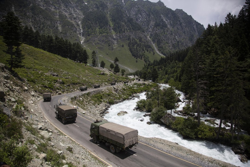 FILE- In this June 17, 2020, file photo, an Indian army convoy moves on the Srinagar- Ladakh highway at Gagangeer, north-east of Srinagar, India, two days after 20 Indian soldiers died in a brawl with Chinese soldiers in the Ladakh region. Indian and Chinese officials are holding talks Thursday, Aug. 20, 2020 to try to resolve a months-long standoff along their disputed frontier, where the two countries have deployed tens of thousands of soldiers.  (AP Photo/Mukhtar Khan, File)