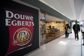 Two people pass the Douwe Egberts Café at Villa ArenA, a mall which specializes in interior design, on the outskirts of Amsterdam, Netherlands, Wednesday, May 7, 2014. Mondelez International Inc. and D.E. Master Blenders 1753 B.V. are combining their coffee businesses. The business will house coffee brands such as Gevalia and Jacobs from Mondelez and Senseo and Douwe Egberts from D.E. Master Blenders, formerly the Sara Lee coffee business. The new company will be called Jacobs Douwe Egberts and be headquartered in the Netherlands. The combined company will have annual revenue of more than 7 billion U.S. dollars. (AP Photo/Peter Dejong)