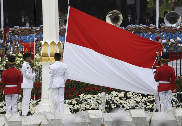 FILE - In this Aug. 17, 2017 file photo, flag bearers hoist the national red and white flag during a ceremony marking the 72nd anniversary of the country's Independence, at Merdeka Palace in Jakarta. Indonesia is accusing the Malaysian organizers of the Southeast Asian Games of negligence after the Indonesian flag was printed upside down in a souvenir guidebook. The mistake, which makes the red-and-white Indonesian flag resemble Poland's, has caused anger in Indonesia where