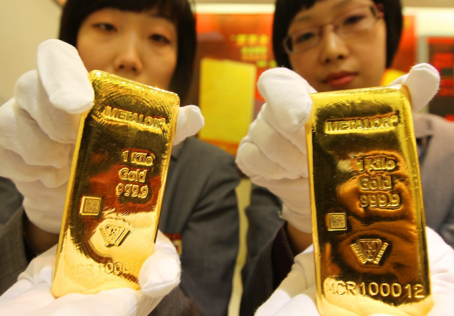 epa02091575 A photograph made available on 25 March 2010 showing two salesgirls show the one kilo Metalor gold bullions made by Swiss company Metalor on the first day of trading in Beijing 24 March 2010.  It is the first foreign brand gold bullion traded in Beijing.  EPA/LAO CAI