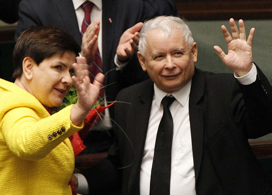 Jaroslaw Kaczynski, the powerful leader of Poland's ruling Law and Justice party and Prime Minister Beata Szydlo wave after her government survived a vote in which the opposition was seeking to oust it, at the parliament buildingin Warsaw, Poland, Thursday, Dec. 7, 2017. (AP Photo/Czarek Sokolowski)