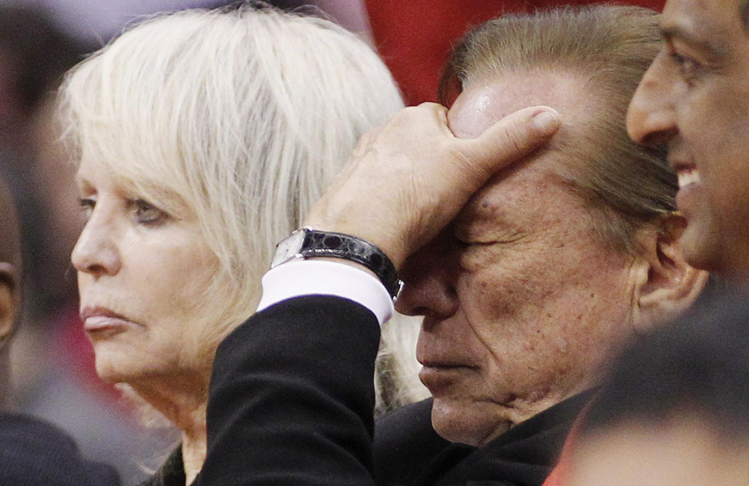 Los Angeles Clippers owner Donald Sterling (R) puts his hand over his face as he sits courtside with his wife Shelly (L) while the Clippers trail the Chicago Bulls in the second half of their NBA basketball game in Los Angeles in this December 30, 2011 file photo. The National Basketball Association banned Los Angeles Clippers owner Sterling from the game for life and fined him $2.5 million for racist comments made public over the weekend, the league's commissioner said on April 29, 2014.  REUTERS/Danny Moloshok/Files   (UNITED STATES - Tags: SPORT BASKETBALL)