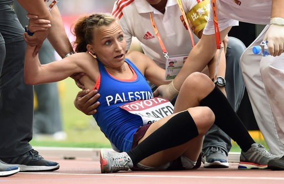 Mayada Al-Sayed of the Palestinian Territories receives medical assistance after finishing the women's marathon at the 15th IAAF Championships in Beijing, China August 30, 2015.  REUTERS/Dylan Martinez
