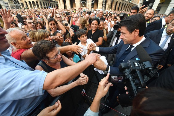 epa07020733 Italian premier Giuseppe Conte (R) speaks with citizens during the one-month anniversary of the tragic Genoa bridge collapse commemorations in Genoa, Italy, 14 September 2018. To commemorate the tragic event exactly one month after the viaduct collapsed, shops closed shutters, tax and bus drivers switched off engines and people stopped in the street to show their respect.  EPA/LUCA ZENNARO