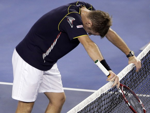 Switzerland's Stanislas Wawrinka rests on the net after losing his fourth round match against Serbia's Novak Djokovic at the Australian Open tennis championship in Melbourne, Australia, Sunday, Jan. 20, 2013. (AP Photo/Rob Griffith)