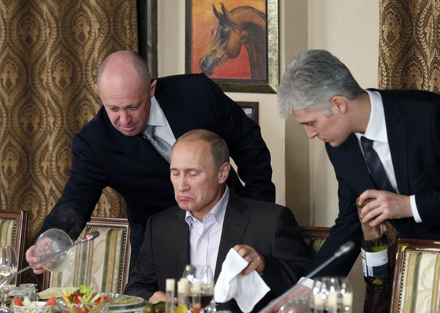 FILE - In this Friday, Nov. 11, 2011 file photo, businessman Yevgeny Prigozhin, left, serves food to Russian Prime Minister Vladimir Putin, center, during dinner at Prigozhin's restaurant outside Moscow, Russia. Multimillionaire St. Petersburg restaurateur Yevgeny Prigozhin is believed to control more than a dozen news portals that attract tens of millions of visitors and serve as an important state propaganda weapon as President Vladimir Putin runs for re-election in the March 18 vote. (AP Photo/Misha Japaridze, Pool, File)