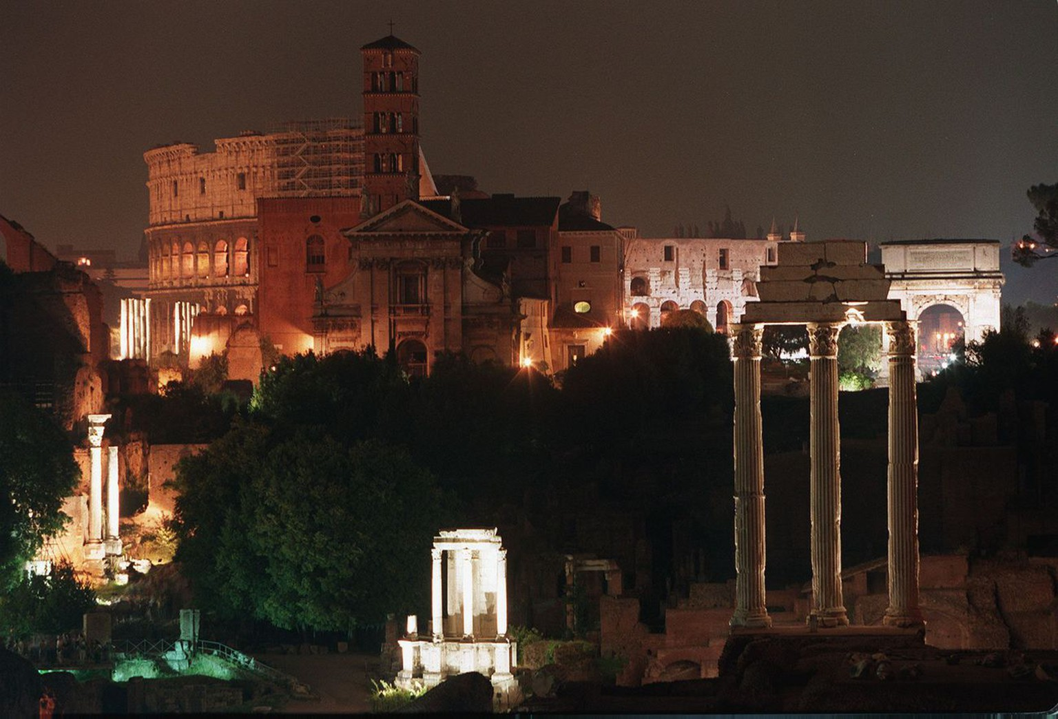 A view over the ancient Forum Romanum illuminated late 21 June, as part of a project that will be carried on until 1999 and will alight all the archeological sites of the eternal city. In the backround is visible the Colosseum and the Arch of Titus (r).