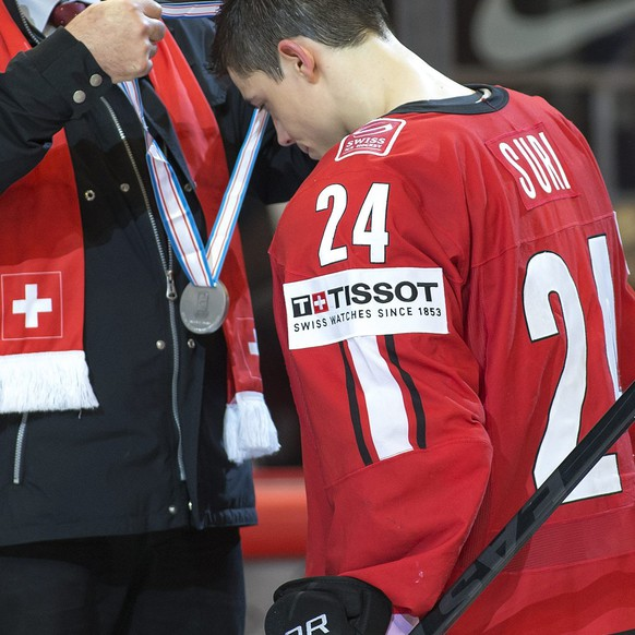 Swiss President Ueli Maurer, left, gives the silver medal to Switzerland's player Reto Suri, 2nd left, and Rene Fasel, 2nd right, President of the International Ice Hockey Federation (IIHF), to Switzerland's player Eric Blum, right, after Swiss team losing against Sweden during the the Gold Medal game between Switzerland and Sweden at the IIHF 2013 Ice Hockey World Championships at the Globe Arena in Stockholm, Sweden, on Sunday, 19 May 2013. (KEYSTONE/Salvatore Di Nolfi)