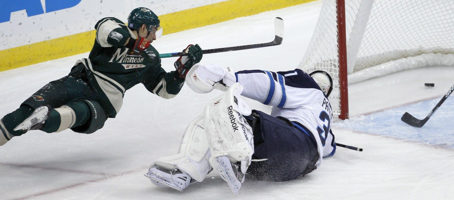 Minnesota Wild right wing Nino Niederreiter, left, of Switzerland, falls as he scores against Winnipeg Jets goalie Ondrej Pavelec, right, of the Czech Republic, during the first period of an NHL hockey game in St. Paul, Minn., Sunday, Nov. 16, 2014. (AP Photo/Ann Heisenfelt)