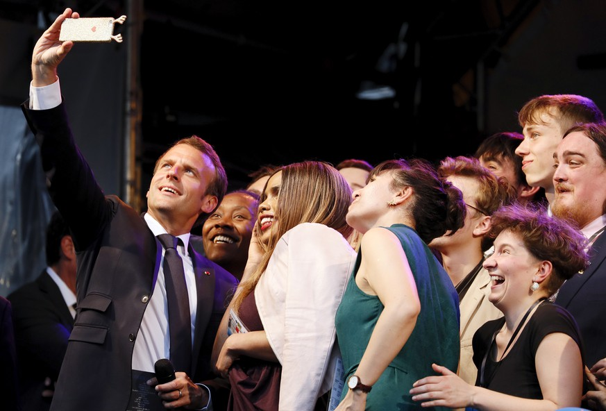 epaselect epa06723419 French President Emmanuel Macron (L) poses for a selfie with National Winners of the European Charlemagne Youth Prize on the eve of the Charlemagne Prize in Aachen, Germany, 09 May 2018. The European Charlemagne Youth Prize awards projects run by and for youth showing an active participation in the development of Europe. Macron was named to receive the prestigious Charlemagne Prize on 10 May 2018. Annually since 1950, the 'Karlspreis' has been awarded to people who contributed to the unity of Europe and is given by the German city of Aachen.  EPA/RONALD WITTEK