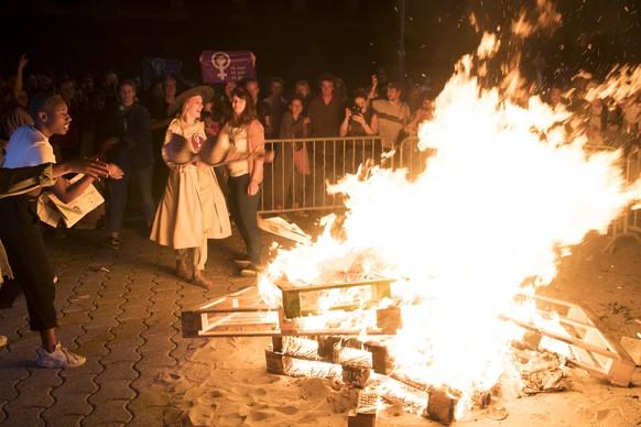 Des femmes brulent un soutien george dans un feu sur la place de la Riponne lors d'une action de lancement de la greve des femmes / greve feministe ce vendredi 14 juin 2019 a Lausanne. (KEYSTONE/Laurent Gillieron)