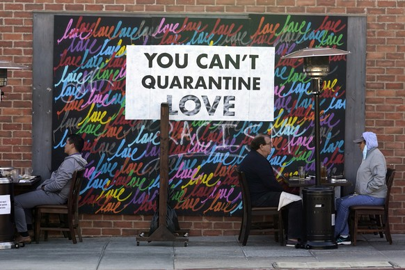 """FILE - In this Nov. 23, 2020, file photo a COVID-19-themed mural reads """"You Can't Quarantine Love,"""" outside of a restaurant in Santa Monica, Calif. Los Angeles County has announced a new stay-home order as coronavirus cases surge out of control in the nation's most populous county. The three-3 week order take effect Monday, Nov. 30, 2020. The order advises residents to stay home """"as much as possible"""" and to wear a face covering when they go out.  (AP Photo/Marcio Jose Sanchez, File)"""