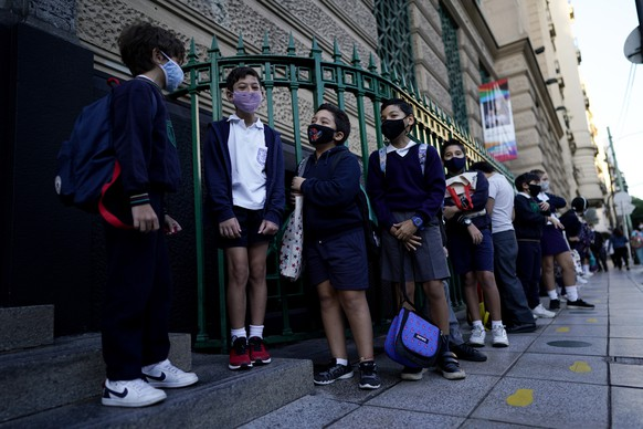 Children line up to enter a school amid the COVID-19 pandemic in Buenos Aires, Argentina, Monday, April 19, 2021. A late-night Sunday ruling by a city court reverted a presidential decree issued last week to suspend in-person classes, generating confusion among families and children. (AP Photo/Victor R.Caivano)