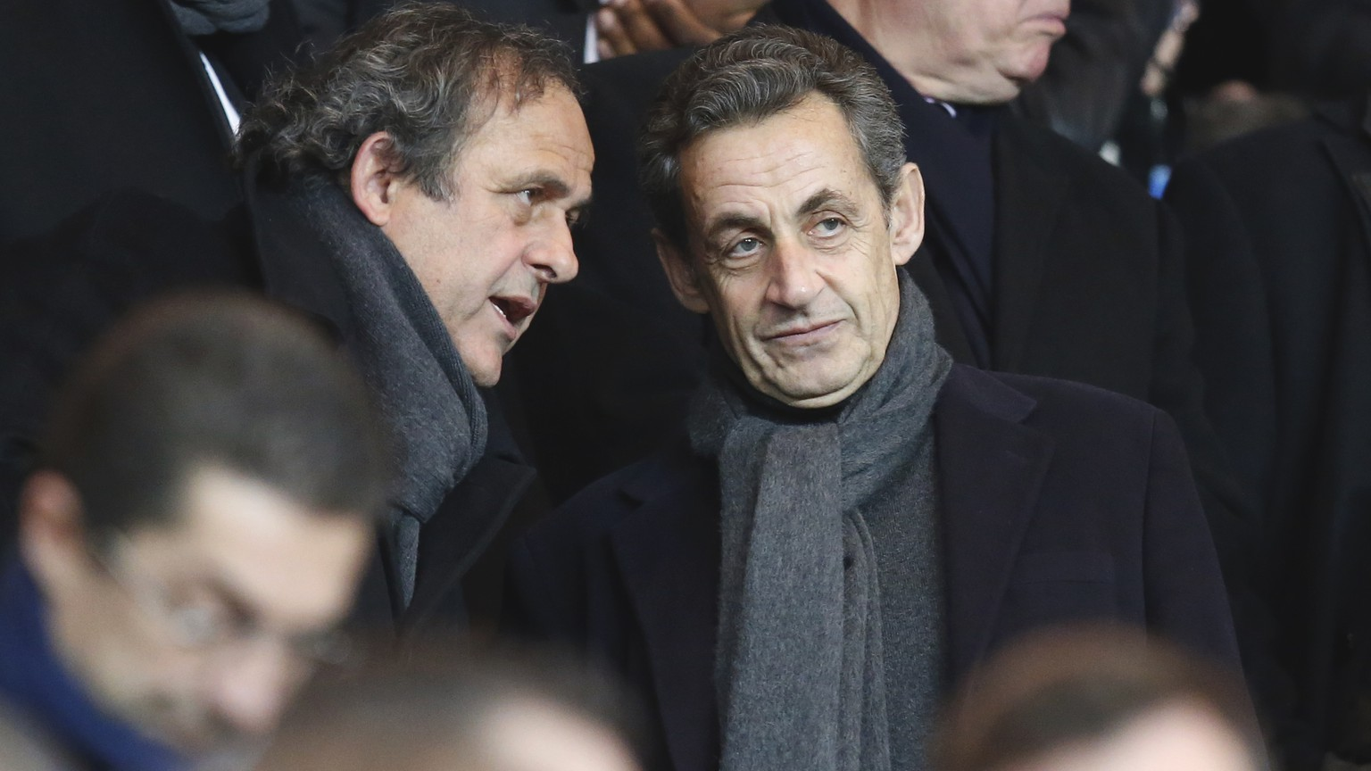 Former French President Nicolas Sarkozy, right, listens to UEFA President Michel Platini, before the Champions League round of 16 first leg soccer match between Paris Saint Germain and Chelsea at the Parc des Princes stadium in Paris, France, Tuesday, Feb. 17, 2015. Striker Edinson Cavani gave Paris Saint-Germain a Champions League lifeline with a second-half equalizer as his team drew 1-1 with Chelsea in the first leg of their last 16 match on Tuesday. (AP Photo/Michel Euler)