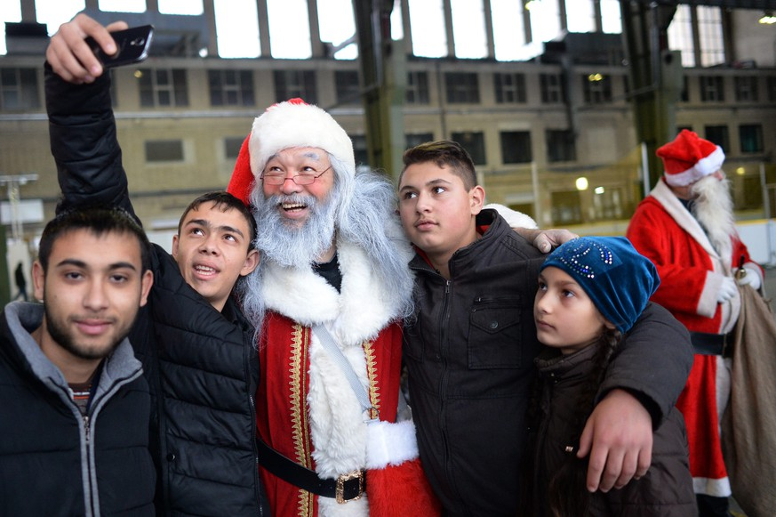 epa05680906 A man dressed as Santa Claus takes a selfie with refugee children at the refugee shelter at Tempelhof airport in Berlin, Germany, 18 December 2016.  EPA/MAURIZIO GAMBARINI