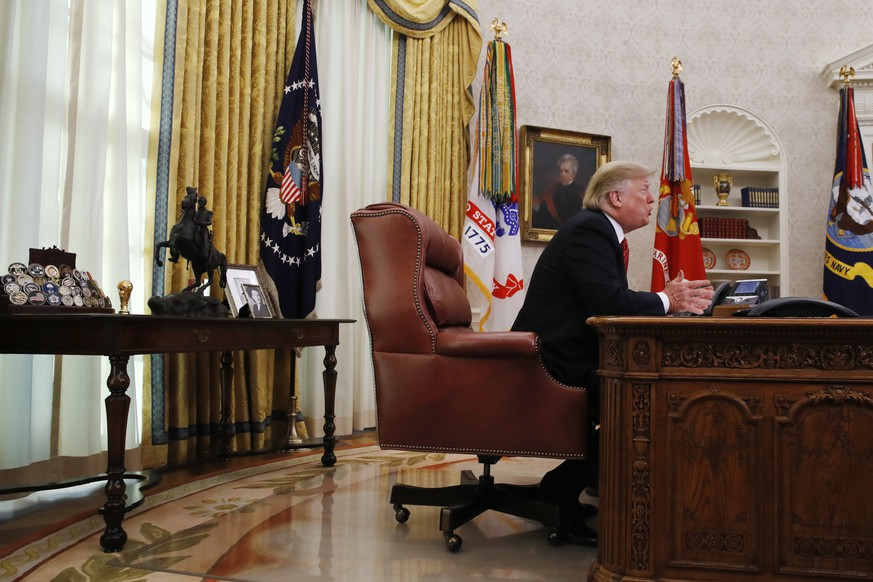 President Donald Trump greets members of the five branches of the military by video conference on Christmas Day, Tuesday, Dec. 25, 2018, in the Oval Office of the White House. The military members were stationed in Guam, Qatar, Alaska, and two groups in Bahrain. (AP Photo/Jacquelyn Martin)