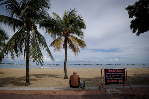 epa08458720 A man looks towards the ocean as he sits at the edge of the beach by a left over sign advising of the beach's closure, on the first day of reopening in Pattaya, Thailand, 01 June 2020. Thailand entered the third phase of the lockdown easing  measures, reopening beaches, massage parlors and a number of other businesses as the number of SARS-CoV-2 coronavirus which causes the COVID-19 disease infections dropped.  EPA/DIEGO AZUBEL