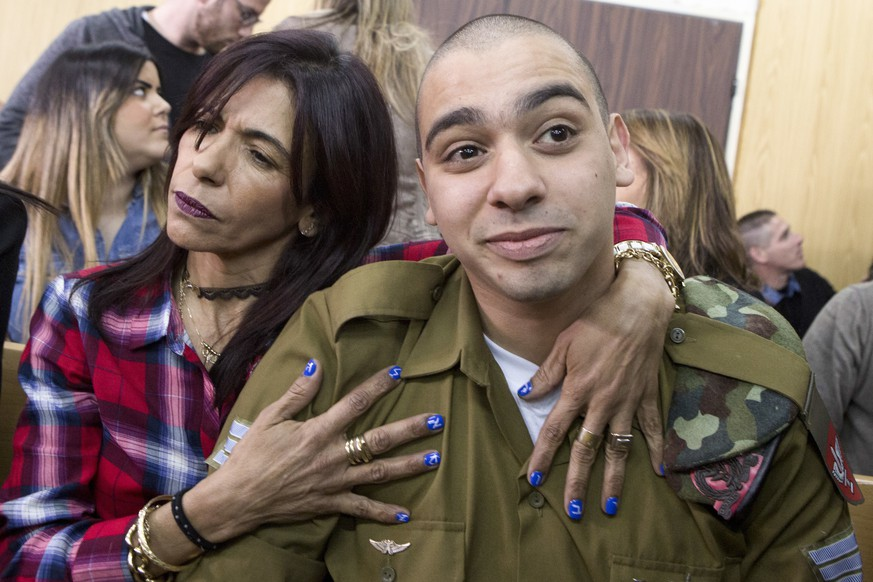 Israeli soldier Elor Azaria is embraced by his mother at the start of his sentencing hearing in Tel Aviv, Israel, Tuesday, Feb. 21, 2017. The court sentenced Azaria to 18 months in prison for the fatal shooting of a wounded Palestinian assailant. The Palestinian, Abdel Fattah al-Sharif, was lying on the ground badly wounded and already unarmed when Azaria shot him in the head. Prosecutors had asked that Sgt. Elor Azaria be sentenced to 3-5 years in prison. (Jim Hollander, Pool, via AP)