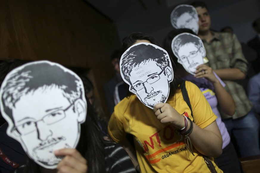 People wear masks with pictures of former NSA contractor Edward Snowden  during the testimonial of Glenn Greenwald, the American journalist who first published the documents leaked by Snowden, before a Brazilian Congressional committee on NSA's surveillance programs, in Brasilia in this August 6, 2013 file photo. Sony Pictures Entertainment has acquired the film rights to journalist Greenwald's book about former Snowden, recruiting producers of the James Bond franchise to bring the story to screen, the studio said on Wednesday.REUTERS/Ueslei Marcelino/Files(BRAZIL - Tags: POLITICS MEDIA ENTERTAINMENT)