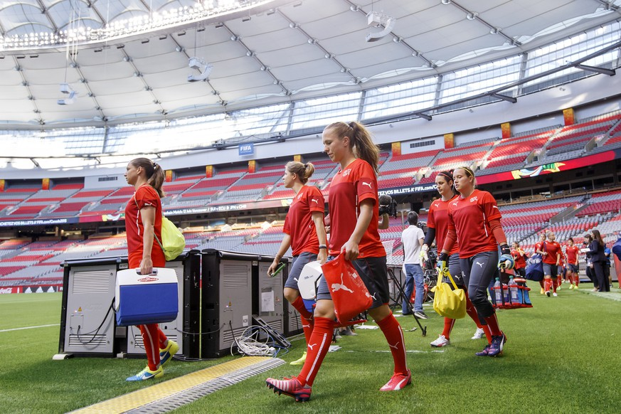 Switzerland's players Fabienne Humm, left, Selina Kuster, 2md left, Lia Waelti, center, goalkeeper Jennifer Oehrli, 2nd right, and goalkeeper Stenia Michel, right, arrive on the pitch of BC Place Stadium for a training session one day before the soccer match against Japan at the FIFA Women's World Cup Canada 2015, at the BC Place Stadium, in Vancouver, Canada, Sunday, June 7, 2015. The Switzerland national soccer team prepare its the FIFA Women's World Cup Canada 2015. (KEYSTONE/Salvatore Di Nolfi)