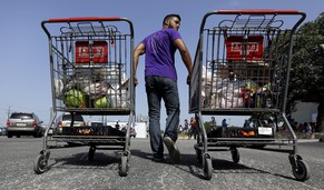 In this July 3, 2014 photo, a volunteer helps distribute groceries at a food bank at the Abundant Life Church in San Antonio. The food bank is cosponsored by the Libre Initiative, partly funded by conservative billionaires Charles and David Koch, which is looking to make inroads with the rising voting block of Hispanics. (AP Photo/Eric Gay)