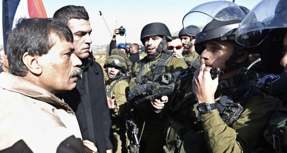 Palestinian minister Ziad Abu Ein (L) argues with Israeli soldiers during a protest near the West Bank city of Ramallah December 10, 2014. The Palestinian minister died on Wednesday shortly after an altercation with Israeli border police in the West Bank during which one of the policeman grabbed him by the neck. Ziad Abu Ein, 55, a minister without portfolio, was taking part in a protest against Israeli settlements when he was involved in clashes with around 30 Israeli troops and border police, a Reuters witness said. It was not clear what caused his death. The Israeli army said it was looking into the incident. Prime Minister Benjamin Netanyahu's Arabic language spokesman said the circumstances leading to the death of the minister were being investigated.  