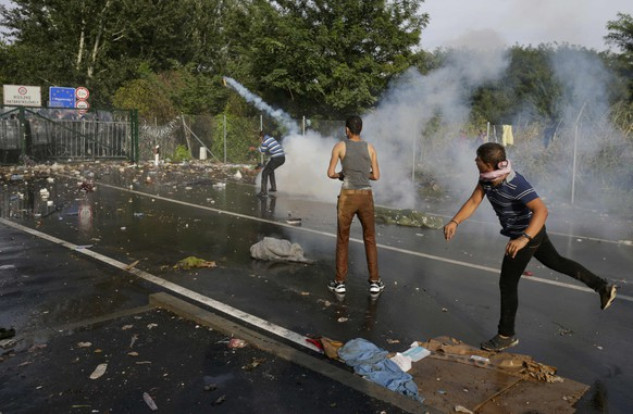 """Migrants react as Hungarian riot police fires tear gas and water cannon on the Serbian side of the border, near Roszke, Hungary September 16, 2015. Serbia on Wednesday condemned Hungary's use of water cannon and teargas against migrants on their border, saying Hungary had """"no right"""" to do so, the Serbian state news agency Tanjug reported. REUTERS/Stoyan Nenov"""