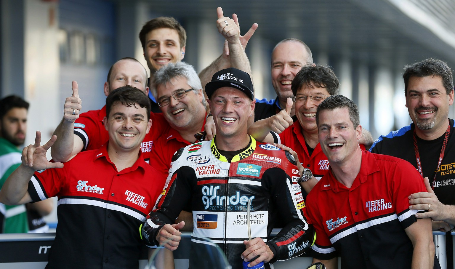 epa05946800 Swiss Moto2 rider Dominique Aegerter (C) celebrates with his team after he finished in third position for Spain's GP race at Jerez de la Frontera's track, southern Spain, 06 May 2017. The race will be held on 07 May.  EPA/JOSE MANUEL VIDAL